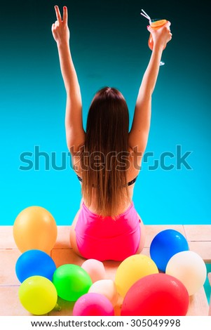 Spa relax and holidays concept. Happy woman in swimsuit back view. Fit female body, girl at poolside with cocktail glass arms raised up in celebration - stock photo