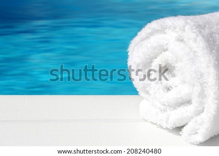 Spa, relax, balneo - rolled towel on wooden desk with blue water - sea background - stock photo