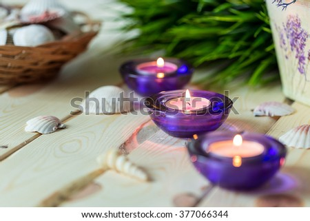 Spa Relax Set, Aromatic Candles in Purple Glass Candlesticks, Green Grass and Shells on Light Wooden Background, Close-up - stock photo
