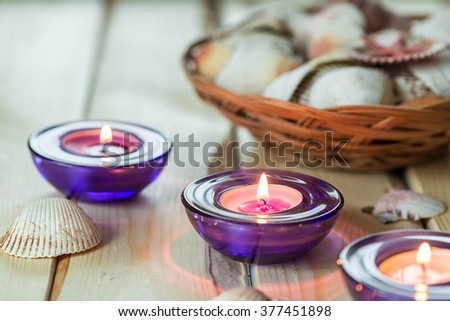 Spa Relax Set, Aromatic Candles in Purple Glass Candlesticks Shells on Light Wooden Background - stock photo