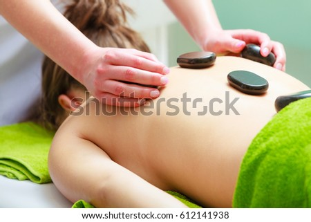 Spa relaxation, healthy pleasure concept. Woman lying on stomach having massage with hot rocks stones in beautician