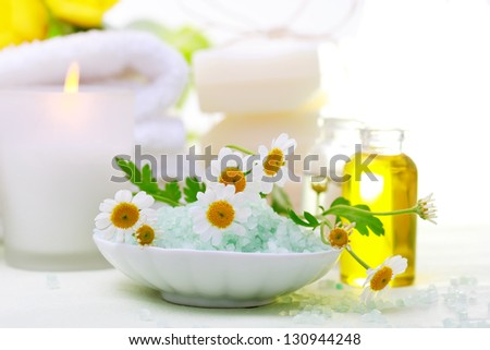 Spa relaxation theme with flowers, bath salt, essential oil, towels and candles - stock photo