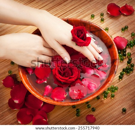 Spa Salon: Beautiful Female Hands with French Manicure in the Bamboo Bowl of Water with Red Roses and Rose Petals on the Straw Mat