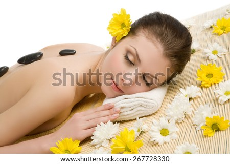 Spa salon: beautiful young woman lying down on the straw mat with flowers and stones. Eyes closed - stock photo