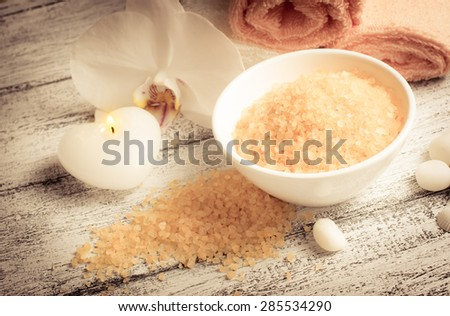 Spa salon with sea salt, towels and burning candle . For this photo applied vignetting effect. - stock photo