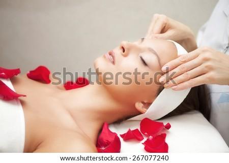 Spa salon: Young Beautiful Woman Having Facial Massage - stock photo