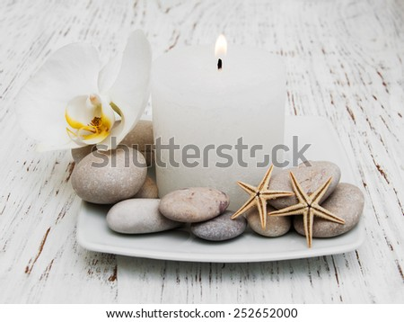 Spa set - candle, orchid flower and pebble on a wooden background - stock photo