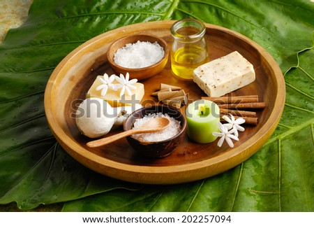 spa set in wooden bowl and green leaf - stock photo