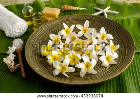 Spa set on banana leaf with frangipani in bowl   - stock photo