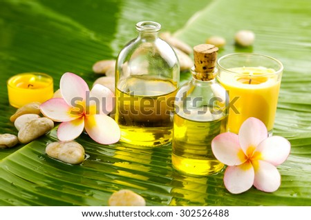 Spa set on banana leaf with pile of stones,candle,oil - stock photo