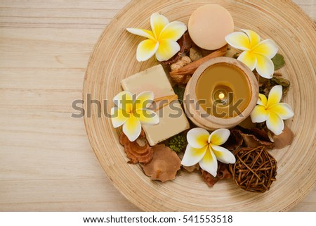 Spa set on wooden background with soap,dry petals, flower ,candleon bowl