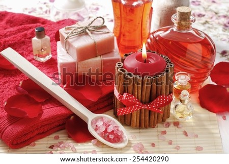 Spa set: scented candle, sea salt, liquid soap and romantic red rose petals - stock photo