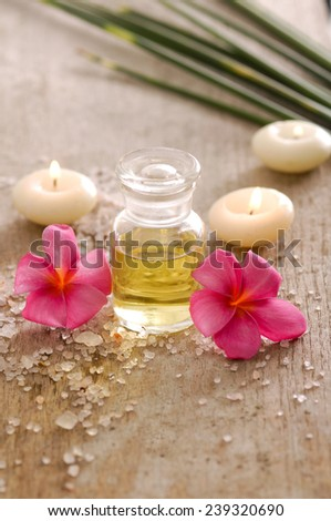 spa set with candle , frangipani and oil with pile of salt on board