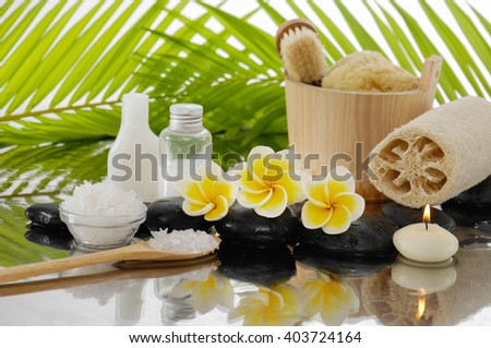 Spa set with salt in spoon, towel, candle ,oil, Frangipani ,stones â??green palm background