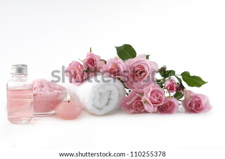 spa setting /bath salt in bowl with pink rose and massage oil ,candle - stock photo