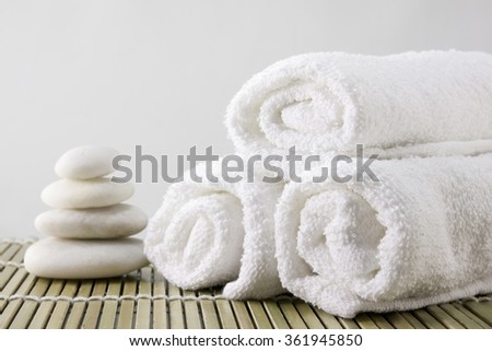 Spa setting decorated with towels and white stone. - stock photo