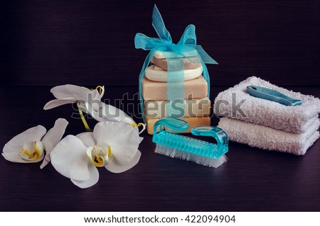 Spa setting in purple and blue colors with different kind of natural soaps, soft towels and orchid on dark wooden background. Tower stack of different handmade soaps. Selective focus.  - stock photo