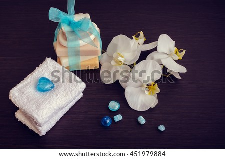 Spa setting in white and blue colors with different kind of natural soaps, soft towels and orchid on dark wooden background. Tower stack of different handmade soaps. Selective focus.  - stock photo