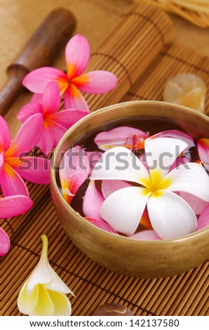 Spa setting, low light with ambient. Frangipani, hot and cold stone on bamboo mat.