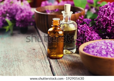 Spa setting on old wooden background. Aroma oil, water with aroma oil, sea salt, flowers. Selective focus, horizontal. - stock photo