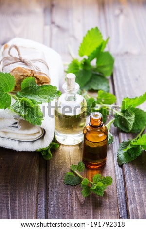 Spa setting on wooden background. Aroma oil, natural handmade soap. Selective focus, vertical. - stock photo