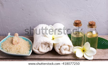 Spa setting. Sea salt with  towels and bottles with oil on vintage wooden background. Selective focus. Place for text.
