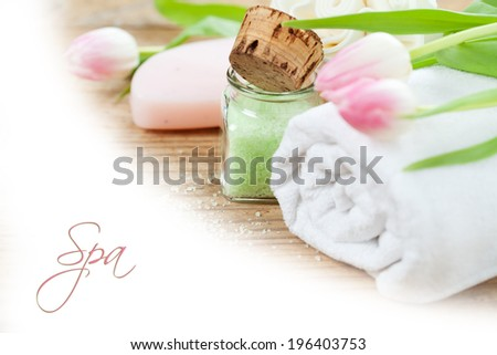 Spa setting with bath accessories and pink tulips on wooden background, text sample