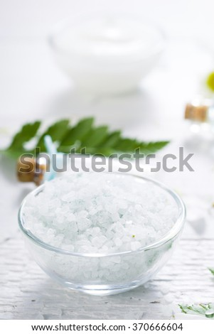 spa setting with bath salt and fern leaves on white wooden table background
