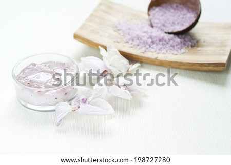 spa setting with bath salts and orchids on wooden table - stock photo