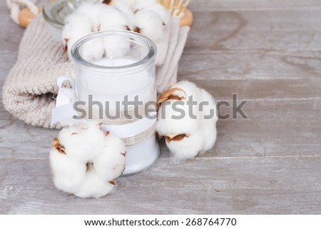 spa setting with candle and  cotton buds on gray table with copy space - stock photo