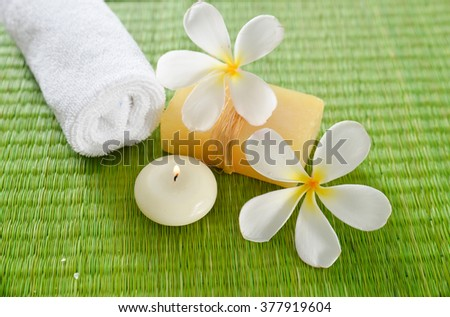 Spa setting with candle, soap ,towel with frangipani - stock photo