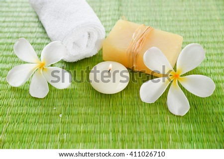 Spa setting with candle, soap with frangipani ,towel on mat  - stock photo