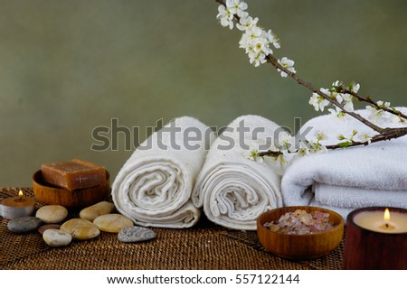 Spa setting with candle ,stones ,towel, soap with mat