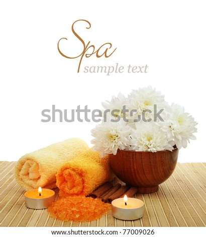 Spa setting with candles, flower, sea salt, towels over white background