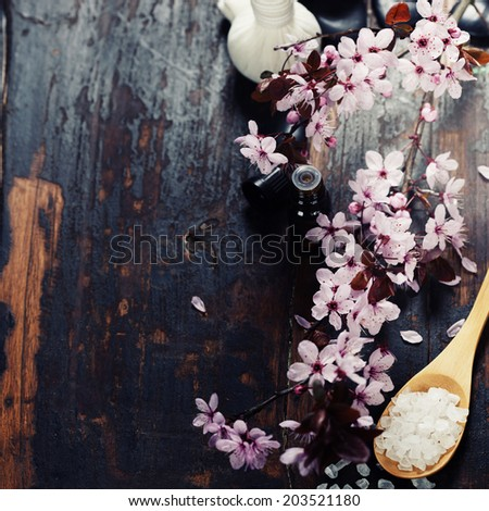 Spa setting with cherry blossoms  over wooden background - stock photo