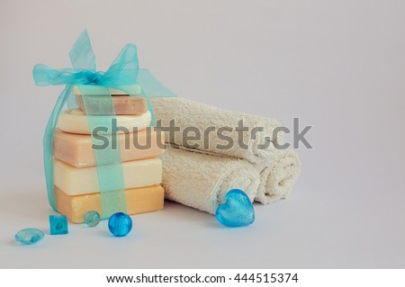 Spa setting with different kind of natural soaps and towels in pastel and blue colors on white background. Tower stack of different handmade soaps. Selective focus. Copy space. - stock photo