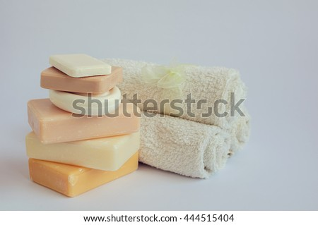Spa setting with different kind of natural soaps and towels in pastel colors on white background. Bar of natural handmade soap. Tower stack of different handmade soaps on white. Selective focus. - stock photo