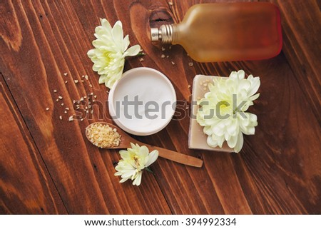 Spa Setting with Essence Oil,Natural Soap  and Sea Salt with flower    on  wooden background  - stock photo