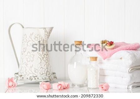Spa setting with fluffy white towels and pamper items - stock photo
