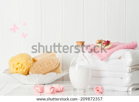 Spa setting with fluffy white towels and pamper items