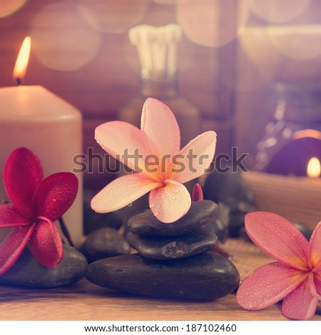 Spa setting with frangipani flower, essential oil, zen stones and aromatic candles on table, Zen concept in vintage retro style. - stock photo