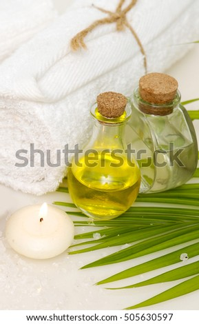 Spa setting with massage oil with towel and palm leaf , candle