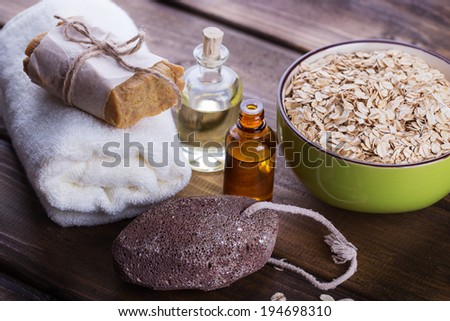 Spa setting with oat flakes on  wooden background. Soap, pumice, aroma oil. Selective focus, horizontal. - stock photo