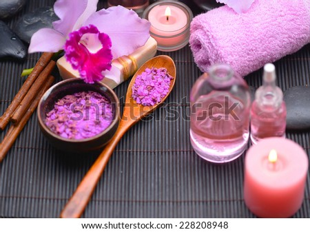 Spa setting with orchid and towel, black stones, oil , cinnamon, on mat - stock photo