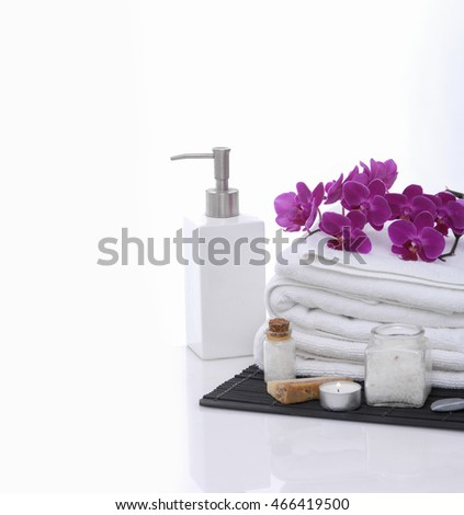 Spa setting with orchid on towel and oil on mat