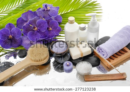 spa setting with palm, towel, salt in bowl, purple orchid