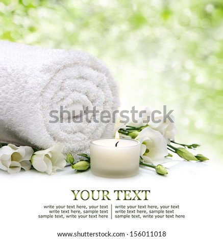 Spa setting with rolled towel, flowers and candlelight - stock photo