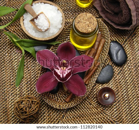 Spa setting with roller towels and salt in bowl and bamboo plant , massage oil ,orchid - stock photo