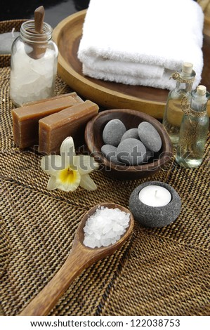 Spa setting with salt in bowl and soap, candle, stones ,orchid