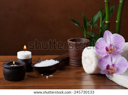 Spa setting with sea salt, candles, towels and orchids.